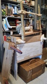 A pile of bookbinding tools: sewing frame, spool of hemp, two book presses, a toolbox, and a trough